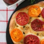 Heirloom tomato focaccia homemade bread on black circular baking stone