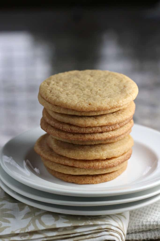 Tall stack of maple cookies on a white plate with a patterned napkin underneath