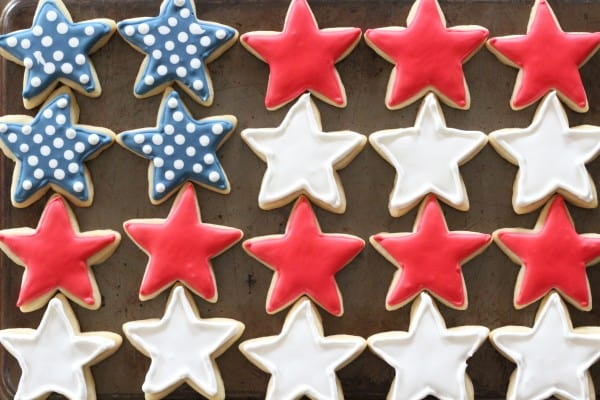 patriotic cookies with red, white, and blue stars lined up in a flag pattern on a baking tray