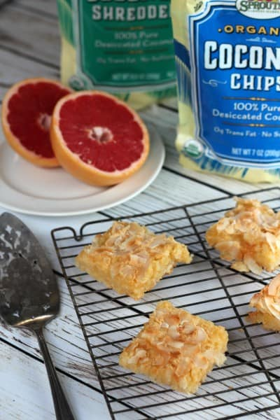 Coconut-grapefruit squares on wire rack with cut grapefruit