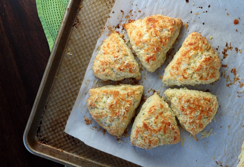 cheese scones baked in a circle on a baking tray and parchment