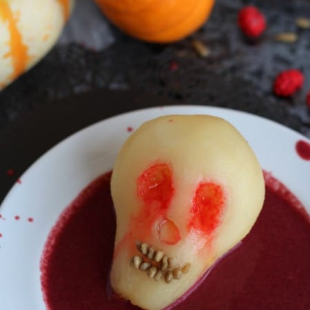 Poached pear for Halloween shaped like a skull in berry sauce