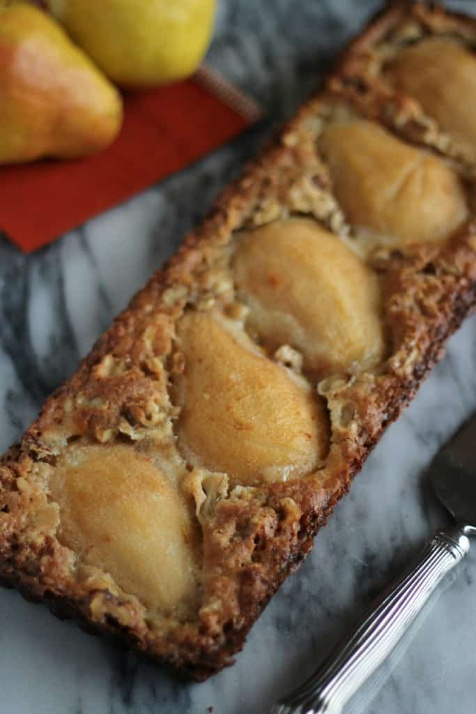 pear and walnut tart GF on marble board with cake server