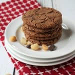 Tall stack of chocolate cookies on white plate with macadamia nuts and chocolate