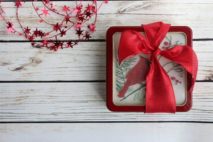 Red ribbon around a square cookie tin
