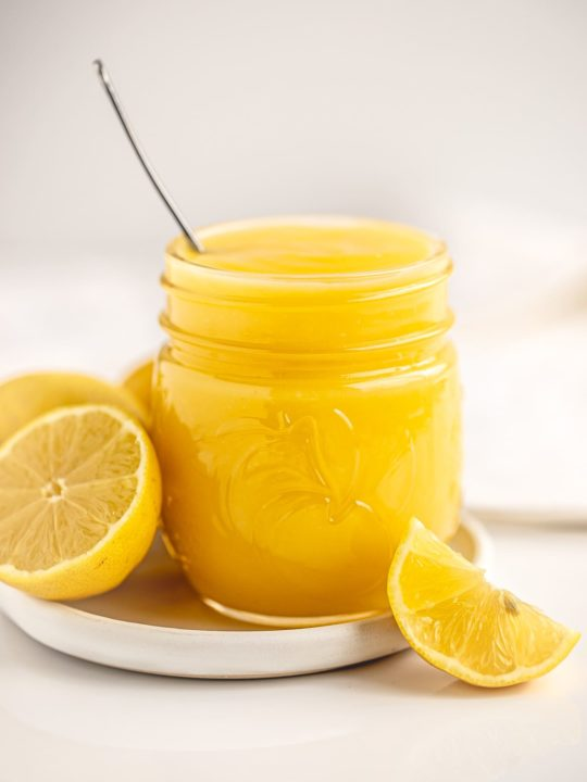 jar filled with bright yellow microwave lemon curd with fresh lemons