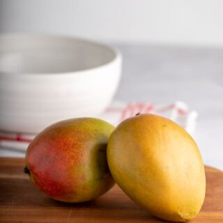 Two mangos on a wooden cutting board