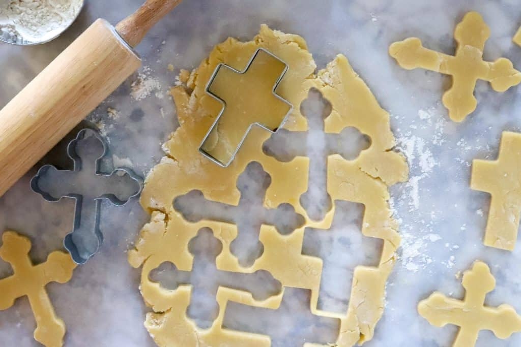 Sugar cookie dough with cross cookie cutters and rolling pin
