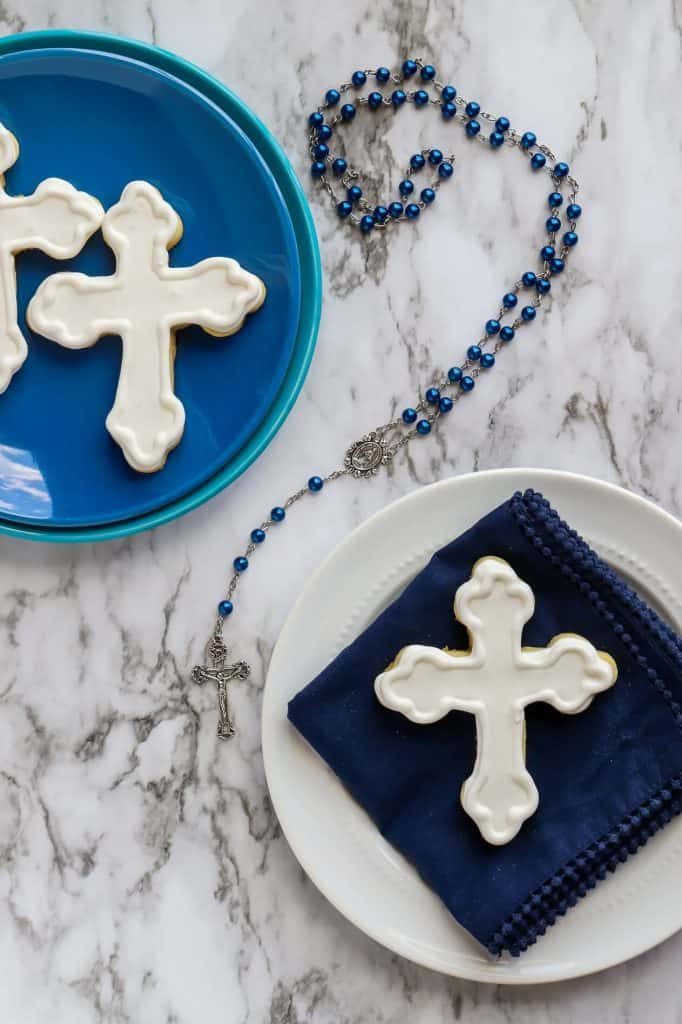 Cross cookies for a first communion celebration on white and blue plates
