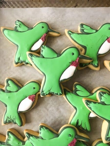Eight green and white decorated hummingbird cookies on parchment paper