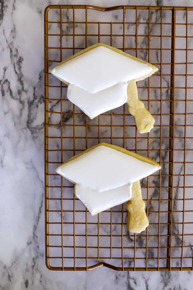 2 cookies shaped like graduation caps with white royal icing