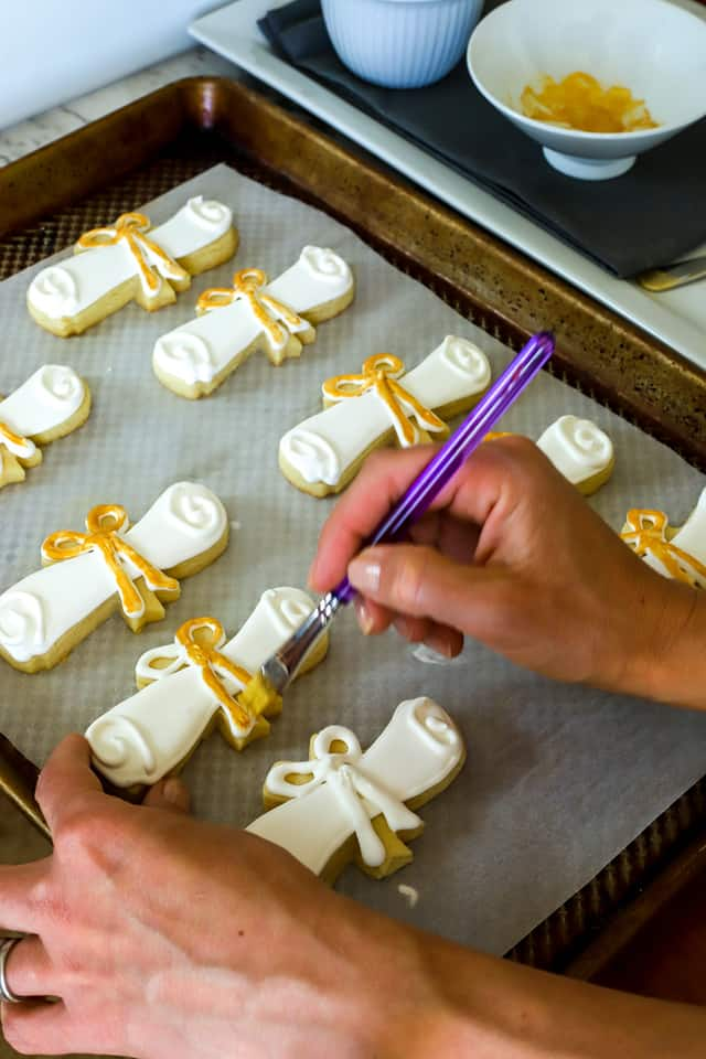 paintbrush adding gold lustre dust to sugar cookies with a paint brush