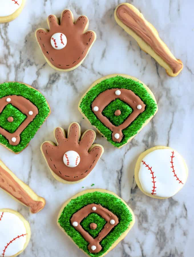 Assortment of baseball cookies including gloves, balls, bats and baseball diamonds
