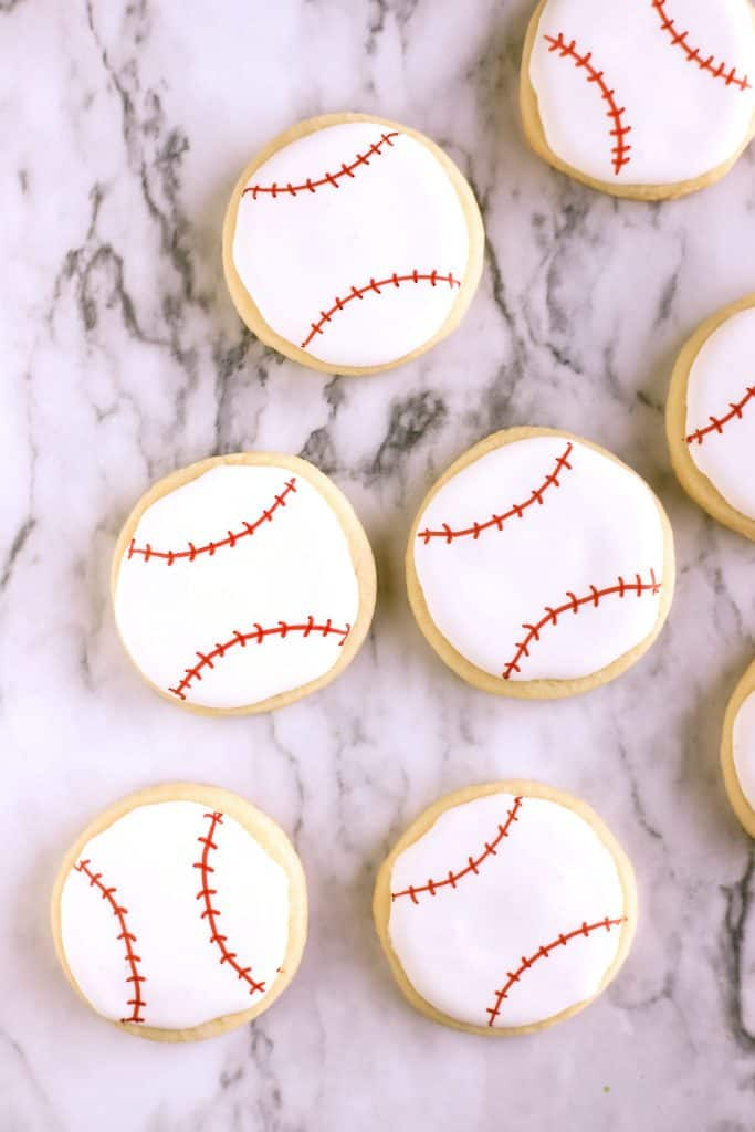 Baseball cookies in the shape of a ball decorated with red lines for the baseball stitches