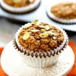 Healthy pumpkin muffin topped with pumpkin seeds or pepitas in a white and aluminum muffin cup on an orange napkin