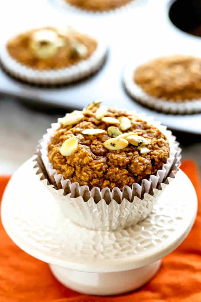 Healthy Pumpkin Muffin on a white and aluminum muffin wrapper cup on a cream cupcake stand