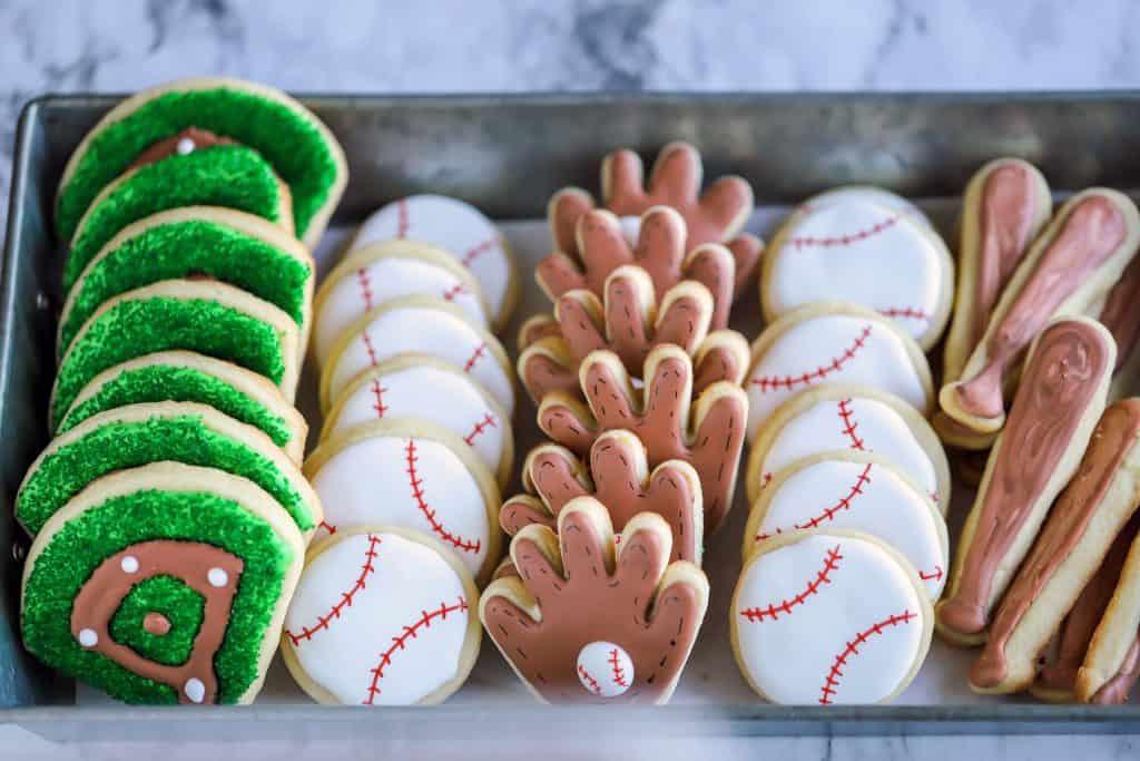 platter of baseball cookies including baseball diamonds, baseballs, gloves and bats