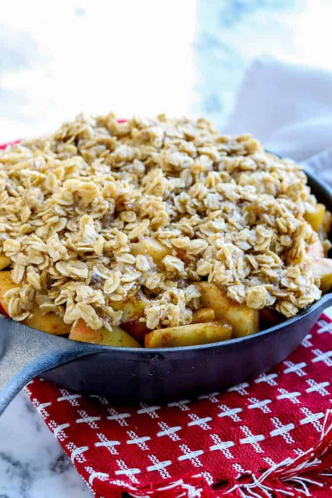 Gluten free easy apple crisp ingredients in a cast iron skillet before baking