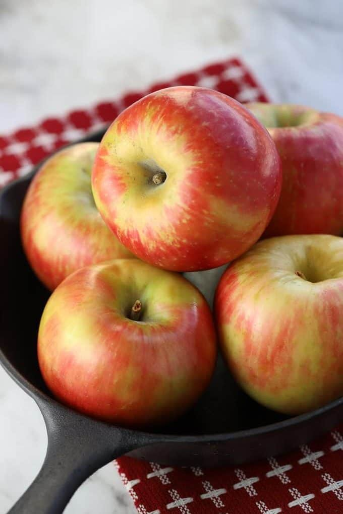 Honeycrisp apples in a cast iron pan sitting on a red and white napkin