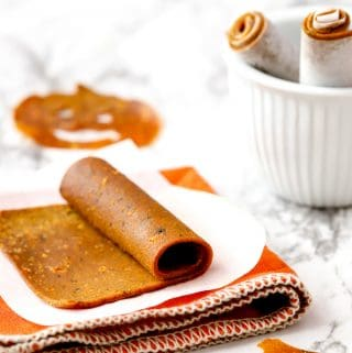 Pumpkin fruit leather roll on parchment with an orange napkin and pumpkin shape in background