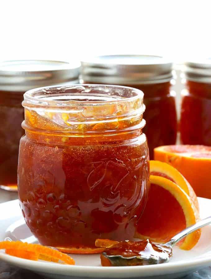 Jar of blood orange marmalade back lit with more jars in background