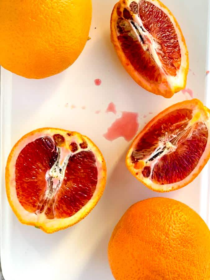 Blood oranges sliced open on white plate with orange juice
