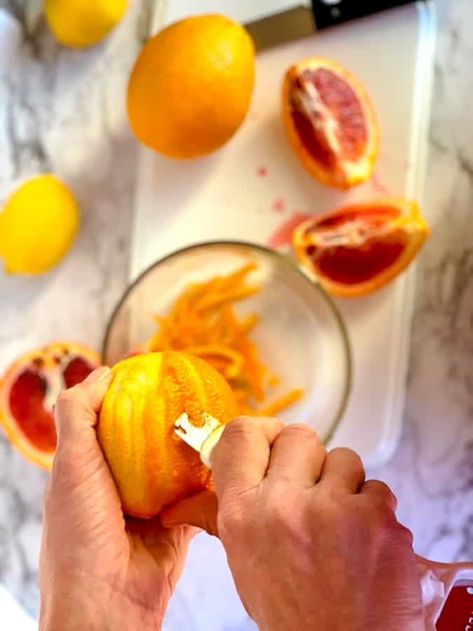 Use a citrus zester to take the zest off of the blood orange in making marmalade