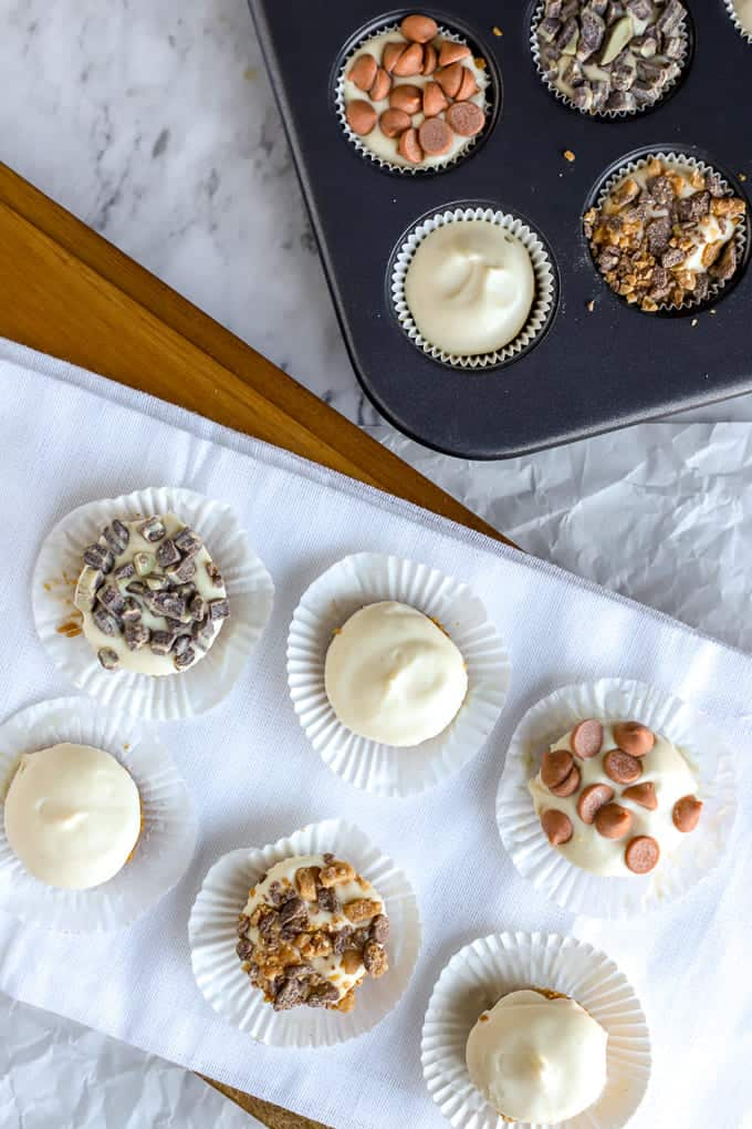 overhead photo of no bake cheesecakes in muffin tin and on white tray