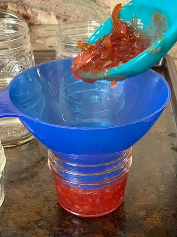 Use a silicone spoon and a jam funnel to ladle the jam into mason jars