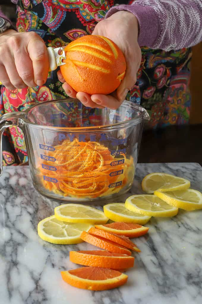 Close up of zesting blood orange into a glass bowl with oranges and lemons on countertop