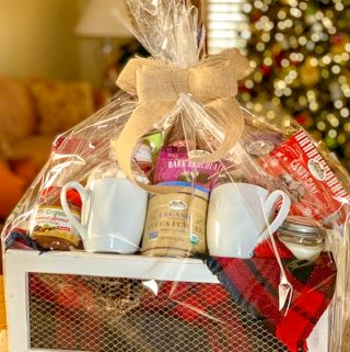 Hot chocolate gift basket wrapped in cellophane and tied with burlap bow