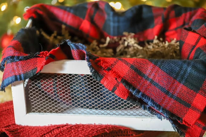 plaid blanket in the bottom of a white crate for gift basket