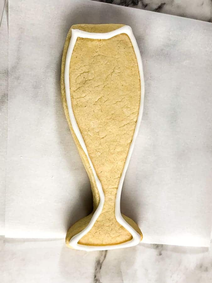 Champagne glass shaped cookie with white outline of icing