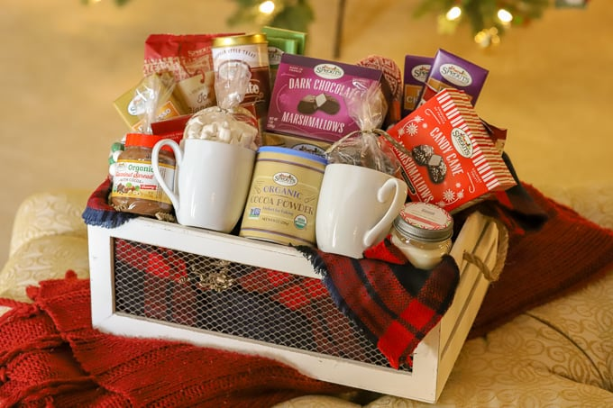 white container filled with chocolate and food items for a homemade gift basket