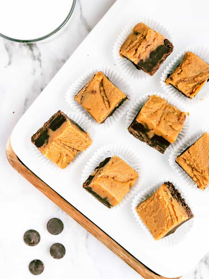 Squares of chocolate peanut butter fudge on a white plate and marble countertop