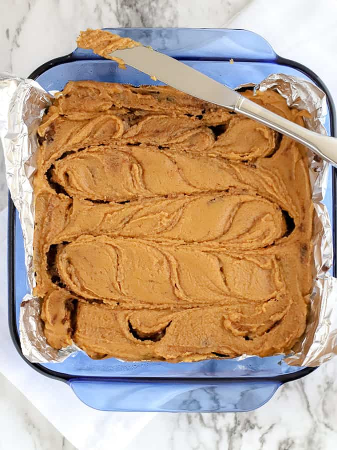 Swirls of peanut butter and chocolate fudge in a blue pan with knife resting on side
