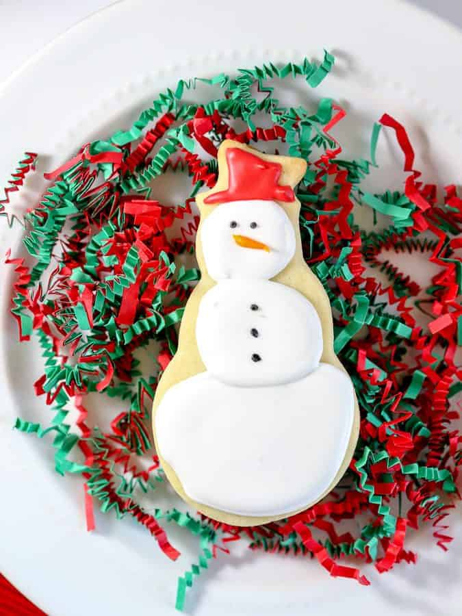 Snowman cookie decorated with royal icing on white plate with red and green confetti