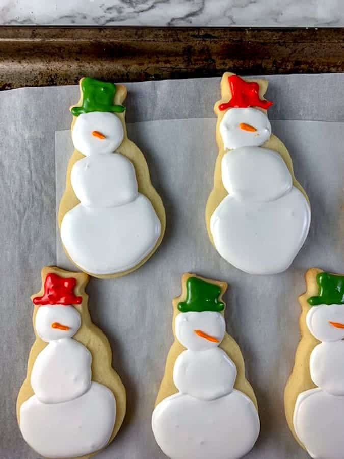 Snowman cut out cookies decorated with royal icing and red and green hats