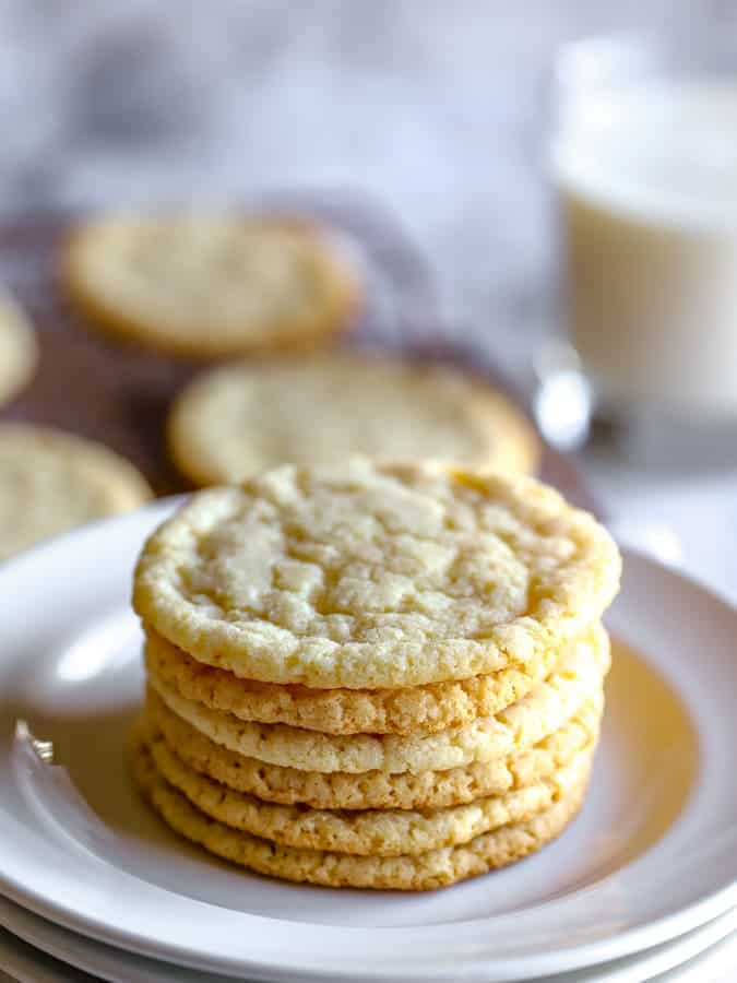 Stack of almond flour sugar cookies on a white plate with milk in background