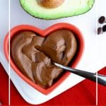 Pinterest image for healthy chocolate avocado pudding in a red heart shaped dish with avocado on white palte