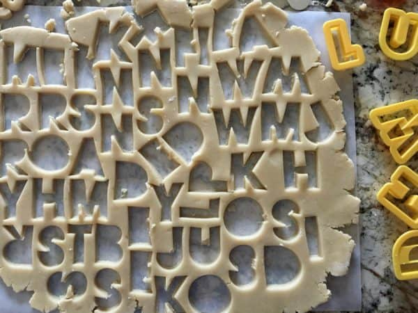 sugar cookie dough rolled out with letter cookie cutters and letters in dough