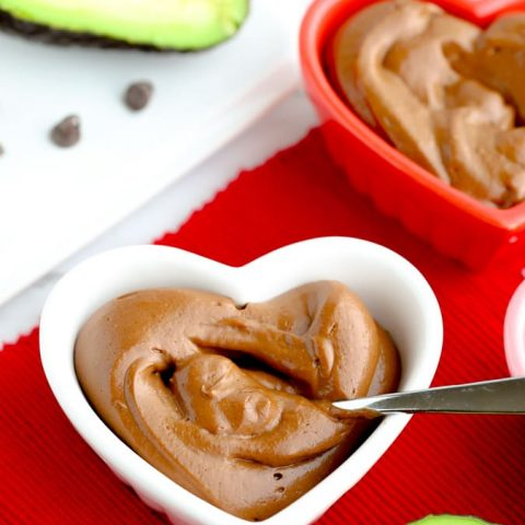 Healthy avocado chocolate pudding in a heart bowl on red napkin