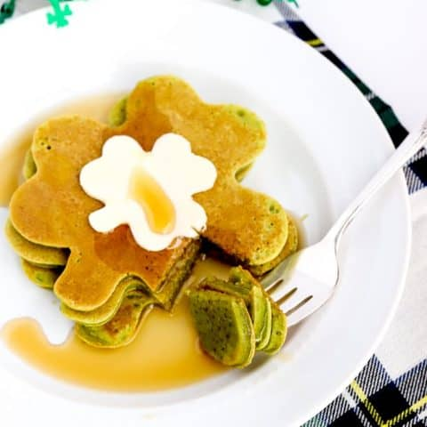 Shamrock shaped spinach pancakes on a plate with butter and syrup