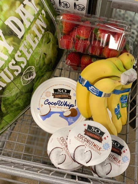 Grocery cart with Sprouts farmers market items bananas strawberries and yogurts