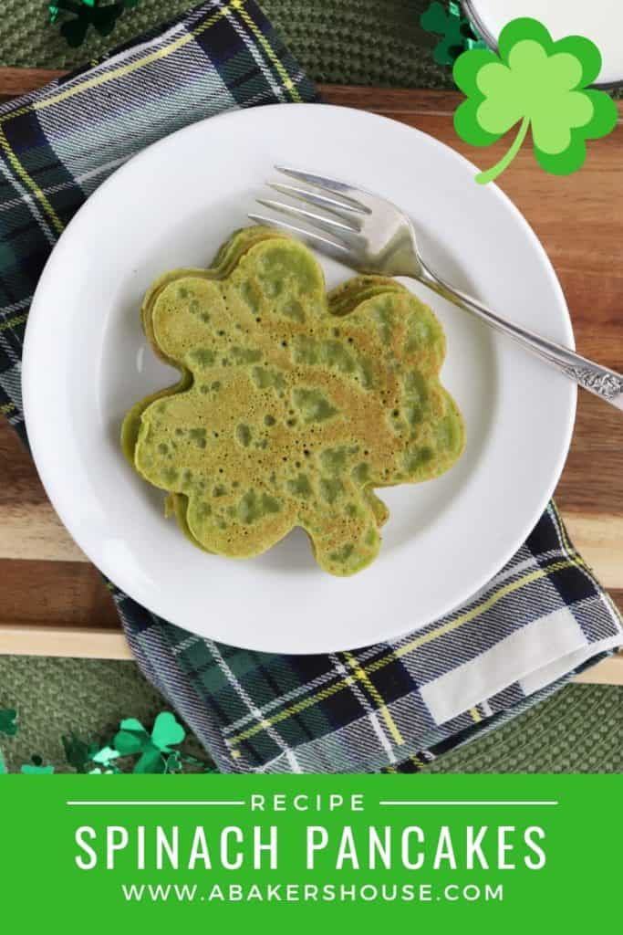 Green pancakes shaped like shamrocks on white plate and plaid napkin