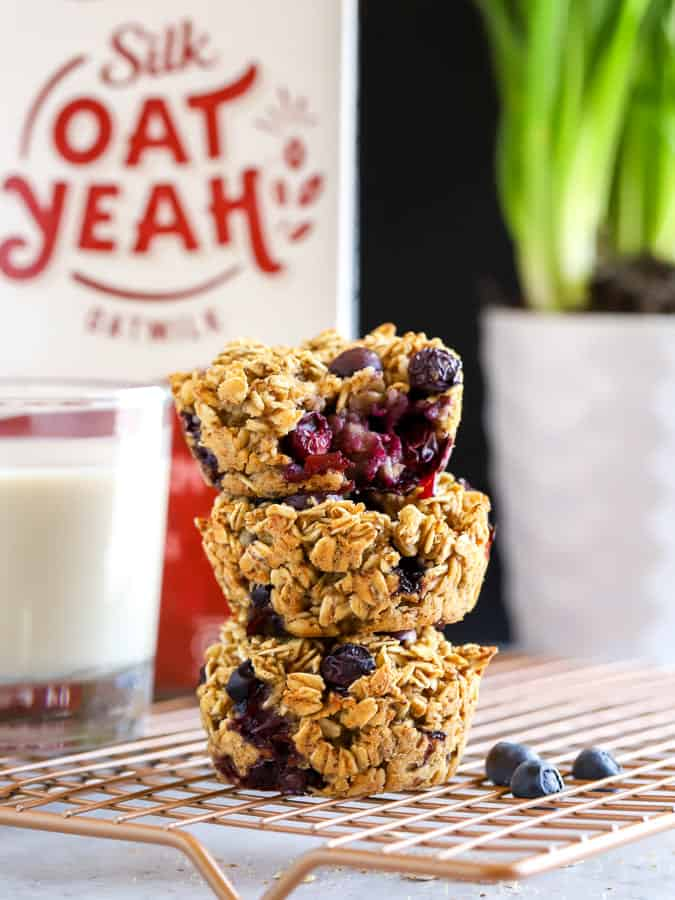 Stack of three baked oatmeal cups with oat Yeah in background