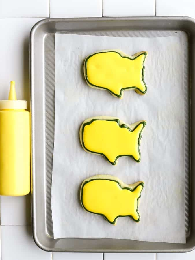 Yellow royal icing filled on USA masters golf cookies