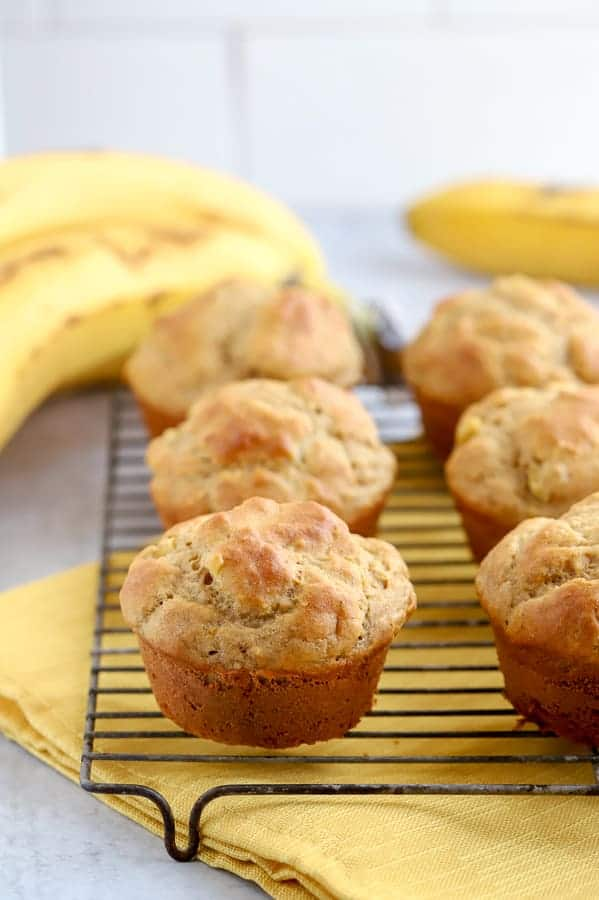 Banana muffins on baking rack with bananas in background