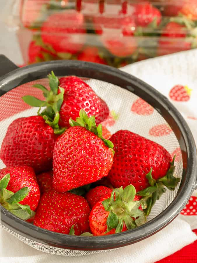 Fresh organic strawberries in a strainer on to of strawberry towel