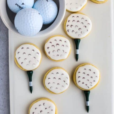 How to make golf ball cookies finished sugar cookies on a white plate with bowl of golf balls